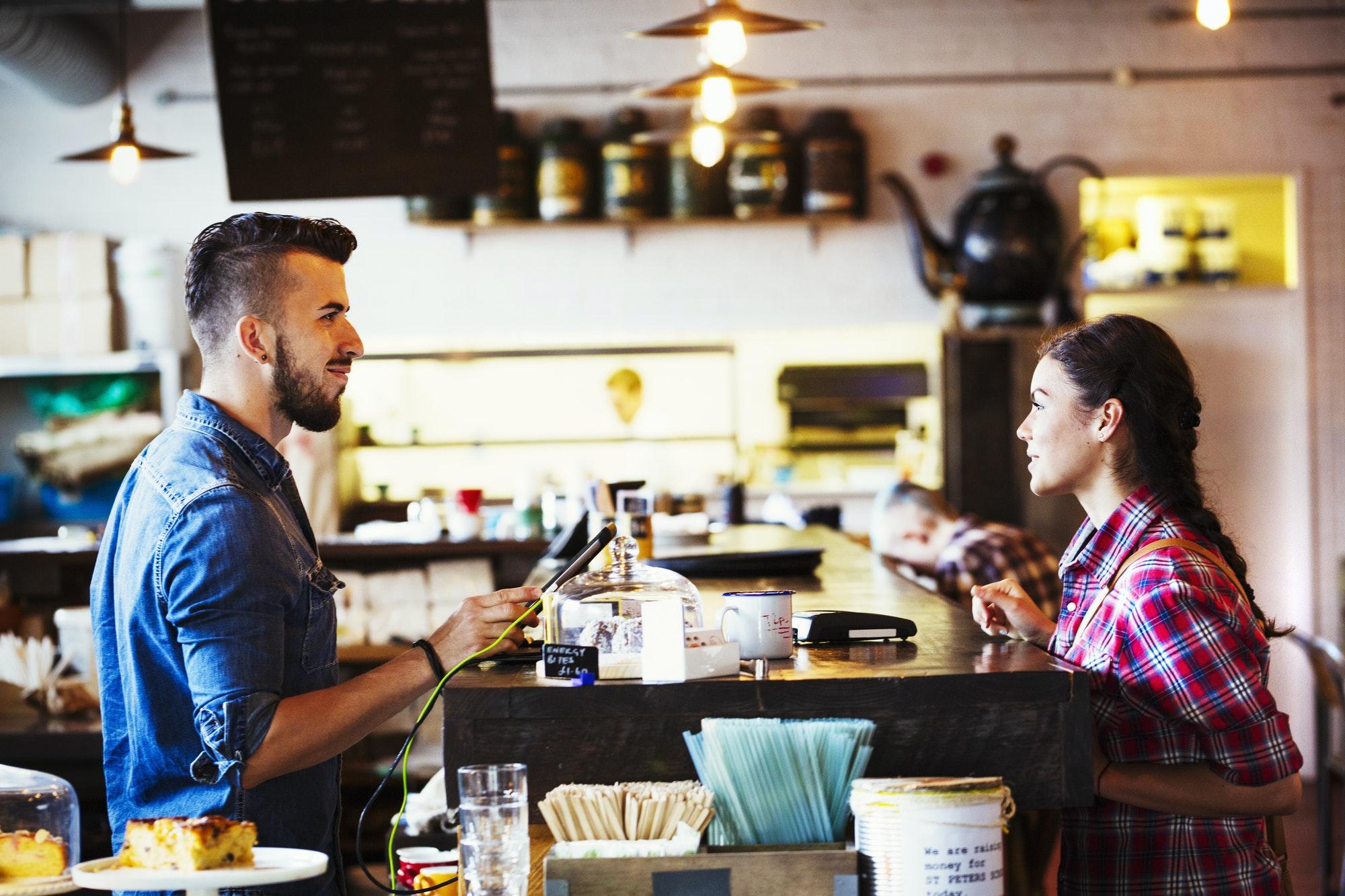 Barista and customer in coffee shop
